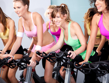 Attractive females on bicycles in a fitness club